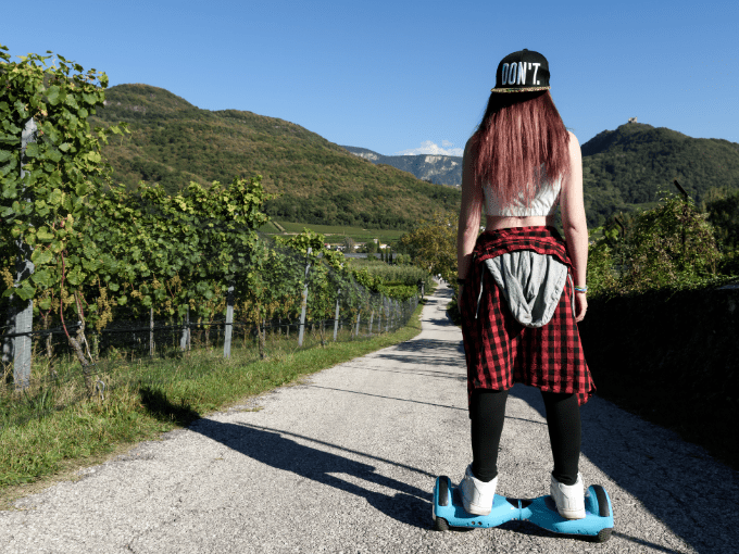 Girl standing on one of the best hoverboard for teenagers on a path with trees with her back to the camera
