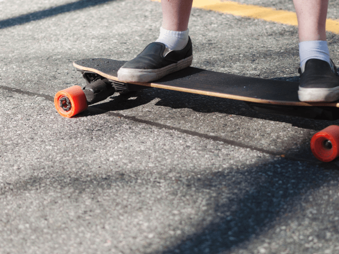 A electric skateboard on the sidewalk